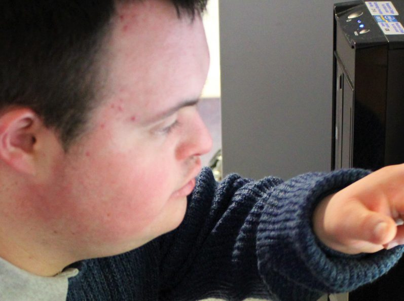 Young man accessing a computer with a touch screen