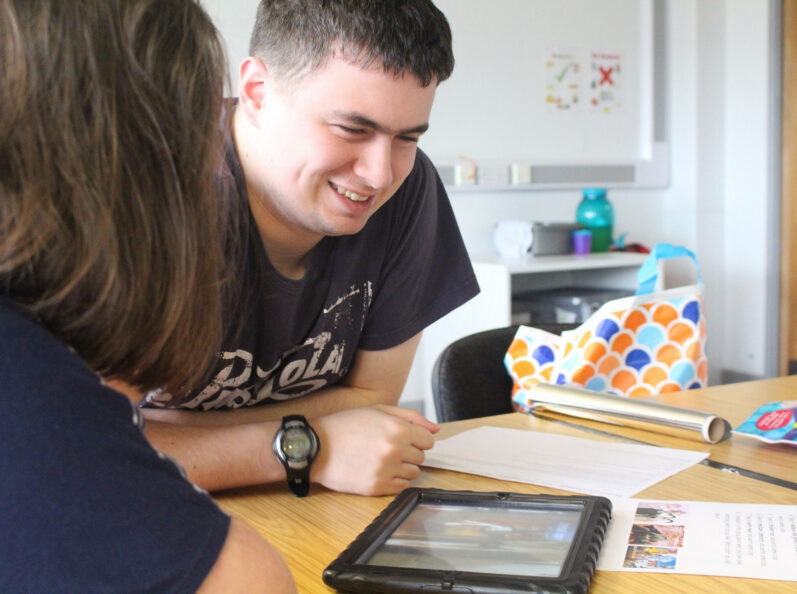 a learner and a tutor have a discussion over an iPad